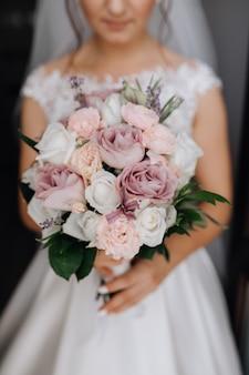 La novia sostiene el hermoso ramo de novia con rosas blancas, moradas y rosas