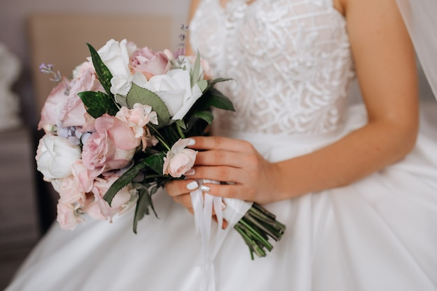 La novia sostiene el hermoso ramo de novia con rosas blancas y rosas