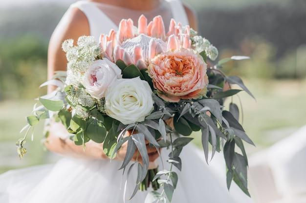 La novia sostiene el hermoso ramo de novia con rosas, eucaliptos y protea gigante