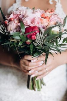 La novia sostiene el hermoso ramo de novia