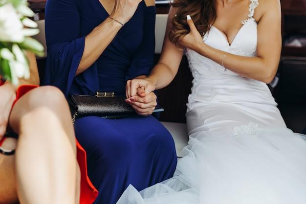 La novia sostiene la mano de la mujer sentada en la mesa.