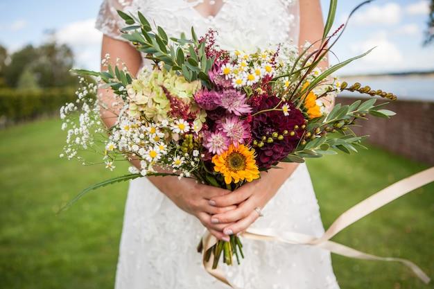 La novia sostiene un ramo de flores frescas de primavera y verano en colores pastel sobre un fondo borroso, enfoque selectivo