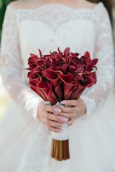 La novia sostiene su flor del ramo de la boda de la cala
