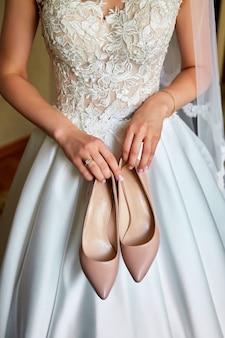 La novia sostiene los zapatos de boda en sus manos.