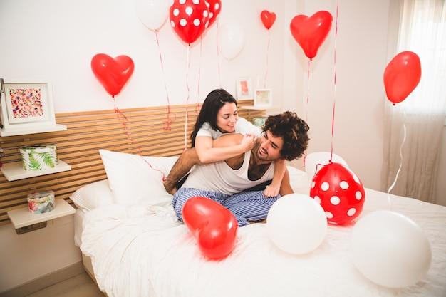 Novia subida en la espalda de su novio en la cama