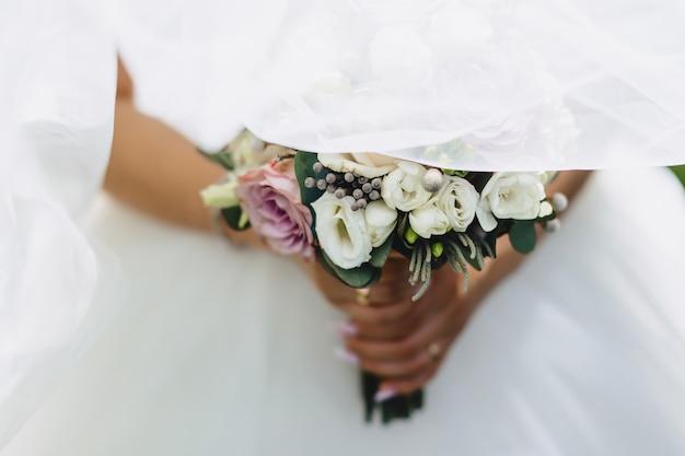 La novia tiene un ramo de boda en sus manos.