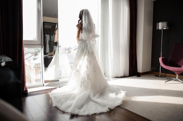 Novia en traje de novia y velo de pie delante de la ventana