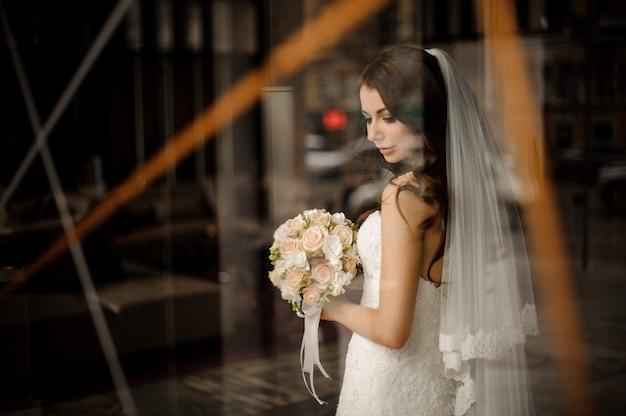 La novia vestida de blanco con ramo de flores sonríe, mirando por la ventana