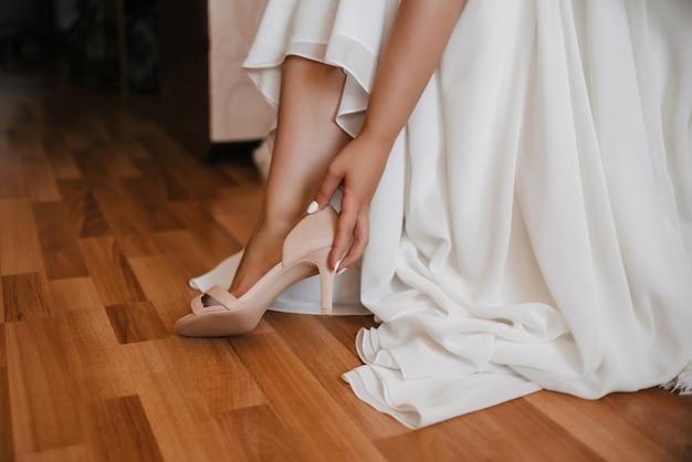 La novia con un vestido blanco lleva un zapato el día de la boda