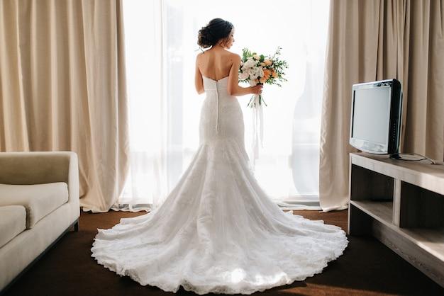 Novia con un vestido blanco con un ramo de flores en una habitación de hotel