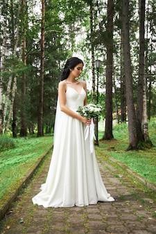 Novia con un vestido blanco y un ramo de flores en sus manos en el parque