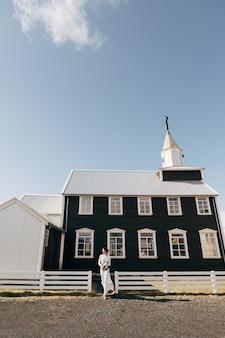 La novia con un vestido blanco con un ramo en sus manos va contra el fondo de las ventanas de madera