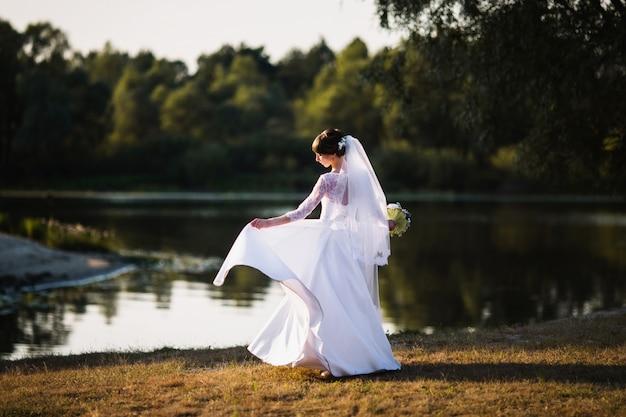 La novia con un vestido blanco sobre fondo de naturaleza. fotografía de boda.