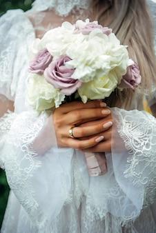 Novia en vestido blanco vintage sostiene un ramo de rosas