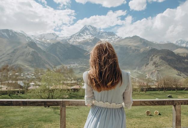 Novia en un vestido esperando al novio mirando a las montañas con picos de nieve