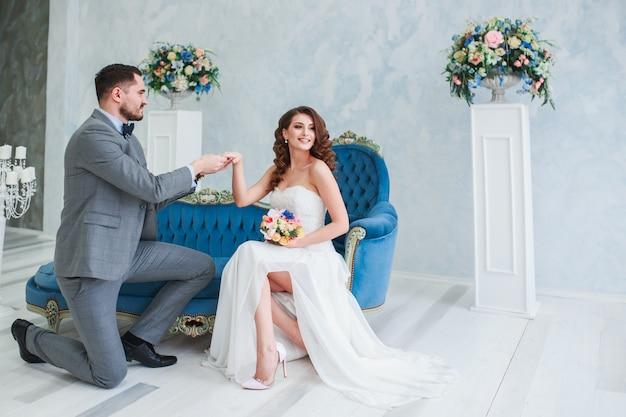 Novia en vestido hermoso y novio en traje gris sentado en el sofá en el interior. estilo de boda de moda
