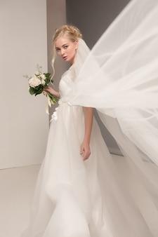 La novia en el vestido hermoso que se coloca dentro en el interior blanco del estudio tiene gusto en casa. tiro de moda estilo boda. joven modelo caucásico atractivo como una novia tierna mirando.