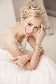 La novia en el vestido hermoso que se coloca dentro en el interior blanco del estudio tiene gusto en casa.