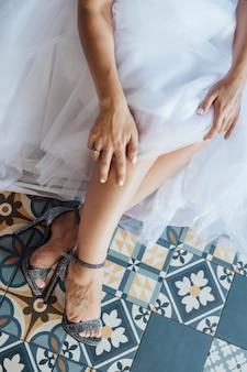 Novia en vestido de novia blanco poniéndose zapatos plateados.