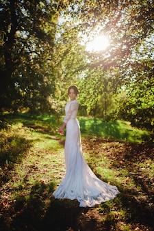 Novia en vestido de novia de pie en el bosque