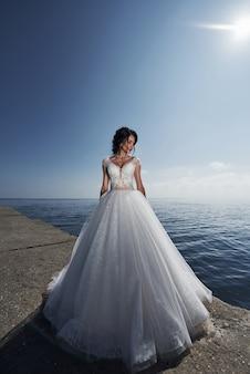 Novia en un vestido de novia en la playa cerca del mar