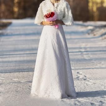 Novia en vestido de novia con un ramo de rosas rojas, boda de invierno