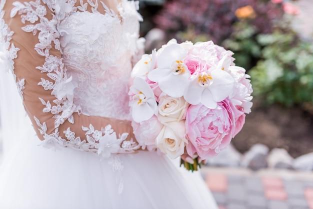 La novia en vestido rico tiene ramo rosado de la boda de orquídeas y peonías