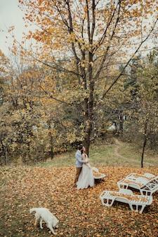 Novia en vestido rosa pálido y novio en chaqueta azul abrazando sobre un césped verde en el bosque de otoño