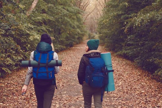 La novia viajera con mochilas fue de excursión por el bosque.