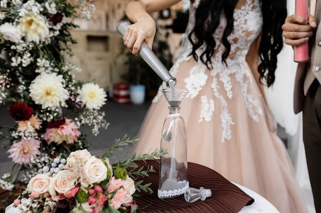 La novia vierte arena gris en una botella