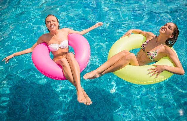 Novias alegres se divierten en la piscina.