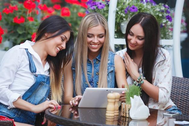 Novias alegres haciendo compras en línea. jóvenes mujeres riendo en la cafetería. sonrientes chicas jóvenes divirtiéndose