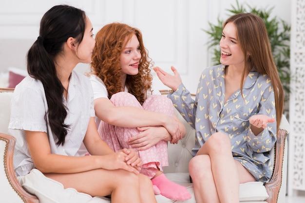 Novias de alto ángulo en el sofá conversando