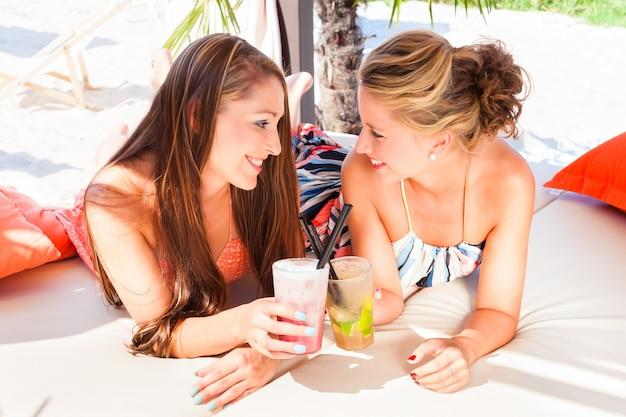Novias en el bar de la playa tomando cócteles.