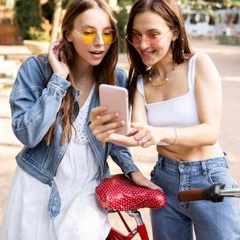 Novias con bicicleta comprobando móvil