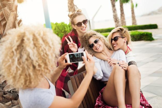 Novias bonitas tomando fotos y selfies relajantes afuera divirtiéndose