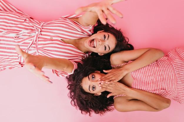 Las novias con cabello oscuro y rizado se divierten en su fiesta de pijamas. la niña riendo se estira hacia mientras su prima se cubre la cara con sorpresa.
