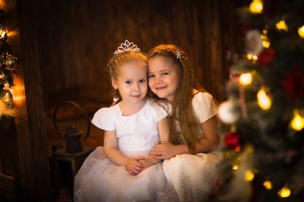 Novias chicas bajo el árbol de navidad, bokeh