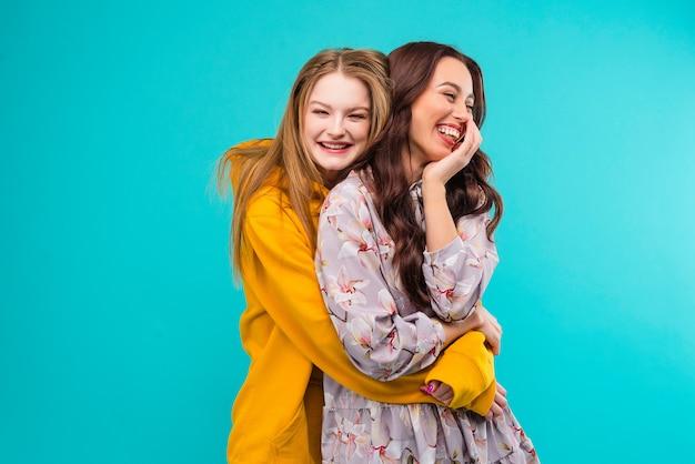 Novias felices abrazándose aisladas sobre fondo azul turquesa