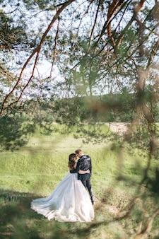 Las novias felices pasan tiempo en el bosque en verano