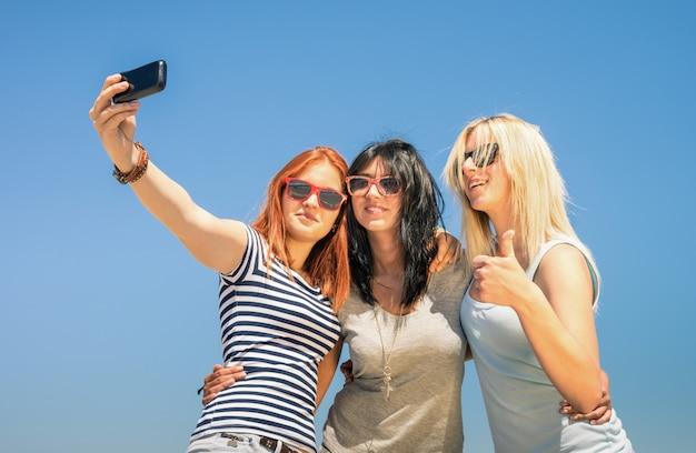 Novias felices tomando selfie contra el cielo azul