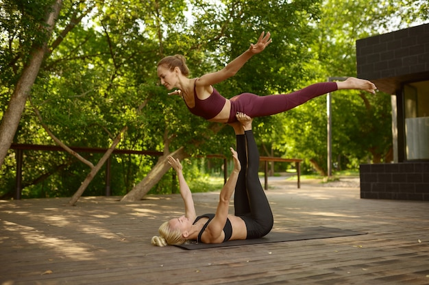 Novias haciendo ejercicio de equilibrio en el entrenamiento de yoga grupal en el parque de verano. meditación, clase de gimnasia al aire libre