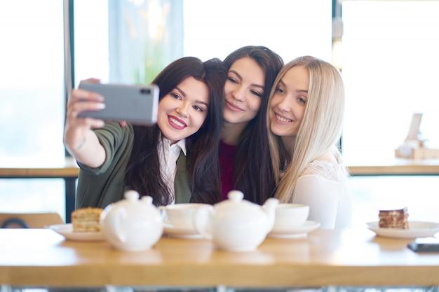 Novias haciendo selfie en café