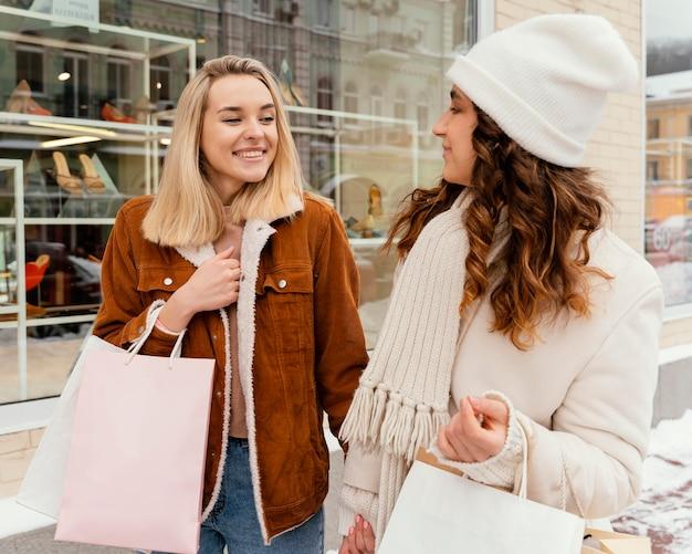 Novias jóvenes al aire libre con bolsas de la compra.