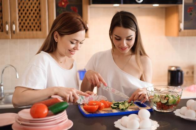 Novias jóvenes cortando verduras con gemelas en una cocina familiar.