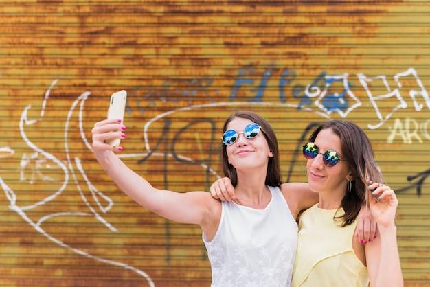 Novias jovenes que hacen el selfie contra la pared de la pintada