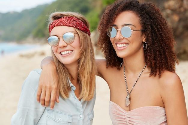 Las novias jóvenes tienen expresiones felices positivas, se abrazan en la playa, tienen una relación interracial. sonriente joven mujer afro de piel oscura admirar la puesta de sol juntos al aire libre. pareja homosexual romántica