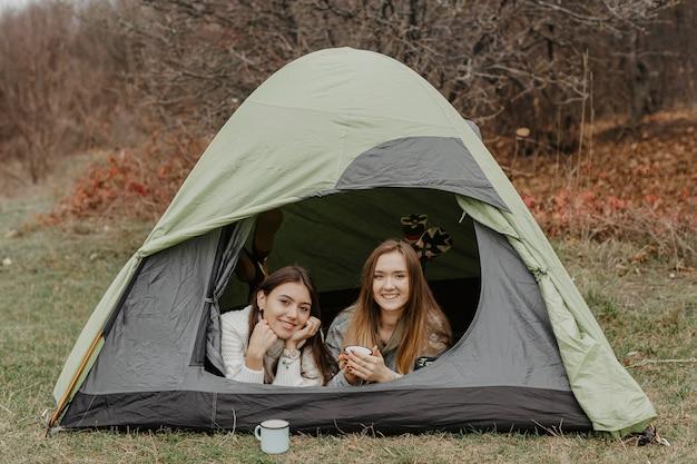 Novias jóvenes en viaje de invierno con carpa