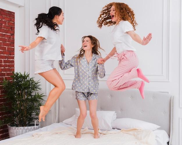 Novias juguetonas saltando en la cama