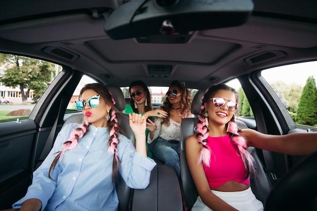 Novias de moda viajando en coche y divirtiéndose juntos.